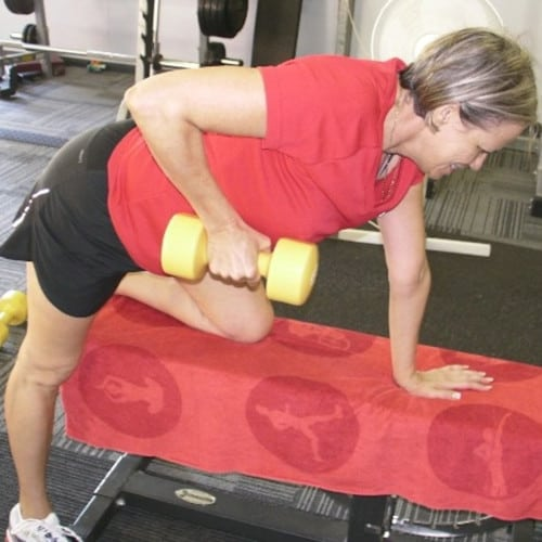 Women lifting hand weight with other hand and knee on bench doing personal training at Shedfit, Wellington Point